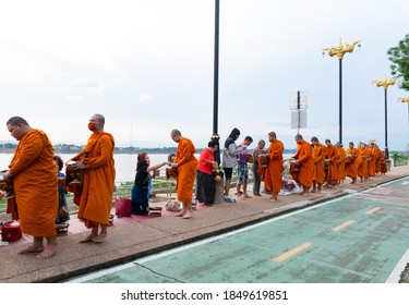 Nakhon Phanom, Thailand- Oct 10, 2020: Thai people make merit by give food to monk at the riverside of Mekong river in morning