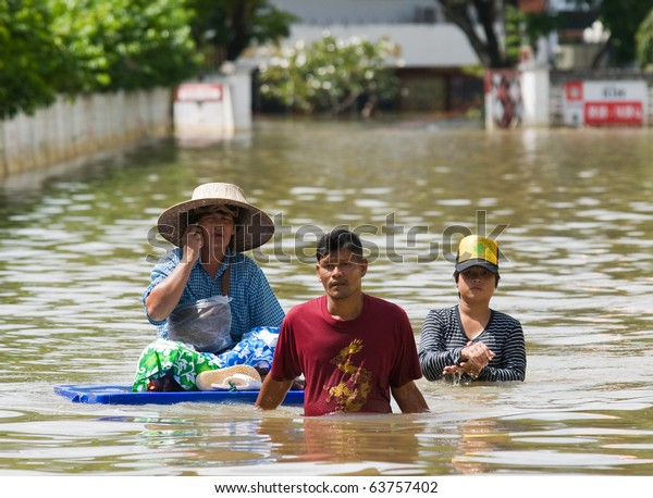 NAKHON RATCHASIMA - OCTOBER 24: People floating their belongings while wading through deep water during the monsoon flooding of October 24, 2010 in Nakhon Ratchasima, Thailand.