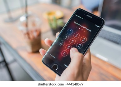 NAKHON RATCHASIMA, THAILAND - APRIL 30, 2016 : Apple iPhone6 held in one hand showing its screen with numpad for entering the passcode
