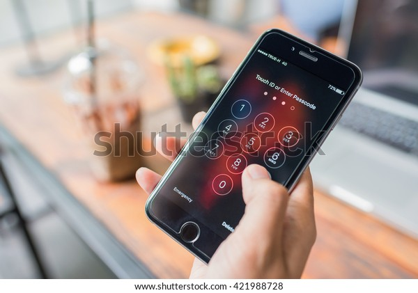 NAKHON RATCHASIMA, THAILAND - APRIL 30, 2016 : Apple iPhone6 held in one hand showing its screen with numpad for entering the passcode. iPhone using.