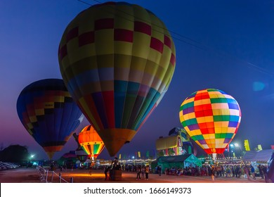 Nakhon Ratchasima, Thailand - February. 3, 2020: Colorful hot air balloons flying above the ground at the food and drink festival in night time.
