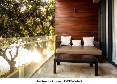 Nakhon Ratchasima, Thailand - January 29, 2021 : Outdoor cozy sofa on terrace with shadow and light on left hand at Atta Lakeside Hotel, Khaoyai national Park a famous tourist landmark