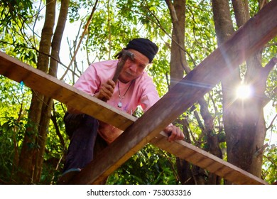 Nakhon Ratchasima, Thailand. November 10, 2017: An Asian man carpenter nails to build a house under the shade at Nakhon Ratchasima, Thailand.