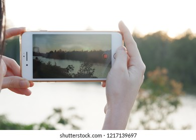 Nakhon Ratchasima, Thailand - Oct 30, 2018 : shot of Woman's hand holding the phone and take a photo of mountain view at Kaoyai - Nakhon Ratchasima, Thailand by the camera app on an Apple iPhone
