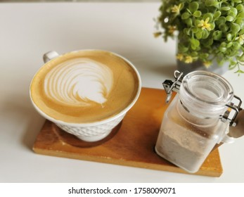 Nakhon Ratchasima/Thailand-June 17, 2020: Coffee art, a cup of latte coffee placed on a wooden tray on a white table of Up to You coffee shop, Korat, Thailand.
