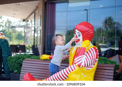 Nakhon Sawan, THAILAND - Feb 01, 2018: Happy cute little Asian toddler baby boy child play with Ronald McDonald in front of McDonald's restaurant