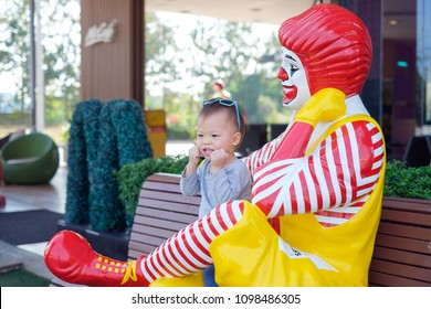 Nakhon Sawan, THAILAND - Feb 01, 2018: Happy cute little Asian toddler boy child play with Ronald McDonald in front of McCafé, McCafé is a coffee-house-style food & beverage chain, owned by McDonald's