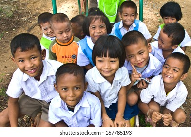 NAKHON SAWAN,THAILAND-JUNE 24: a group of happy unidentified Thai children sitting on the playground with smile on faces. On June 24,2010 in Nakhon Sawan,Thailand.