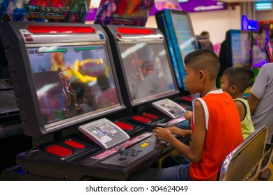 Nakhon Si Thammarat, 27 june 2015: Boys play fighting game on arcade machine in Tesco Lotus supermarket at Nakhon Si Thammarat, Nakhon Si Thammarat province, Thailand.
