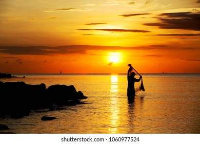 NAKHON SI THAMMARAT, MAY 17,2015; Silhouette of the fisherman throwing net in sea on the sun rises in Nakorn si Thamarat,THAILAND.