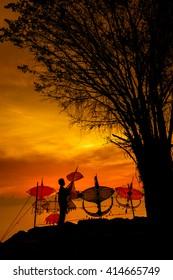 "NAKHON SI THAMMARAT, THAILAND - MAY 1, 2016: Morning landscape at ""Nai Tung Village"" atmosphere of a seaside village, children playing kites under the tree, Nakhon Si Thammarat, Thailand."