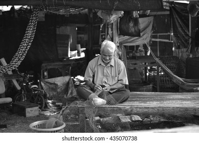"NAKHON SI THAMMARAT, THAILAND - MAY 1, 2016: An old man was repairing a ship at ""Nai Tung Village"" atmosphere of a seaside village, the local professional fishing, Nakhon Si Thammarat, Thailand."