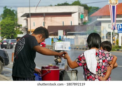 NAKHON SRI THAMMARAT, THAILAND -JUNE 27, 2016: Mother holding a child bought sticky rice, grilled pork.