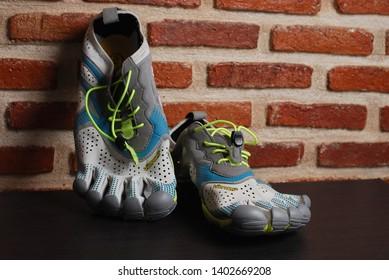 Nakhonpathom, Thailand - May 16, 2019 : Vibram V - Run. Natural performance running shoe's with grunge wall background. Running shoe's for barefoot runner.
