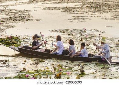 NAKHONPATOM, THAILAND - Apr 15, 2017 : Tourists on wooden boat visiting sea of red lotus water lily in banglen