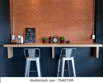 Nakhonphanom,  Thailand - August 28 2017: Black and brick coffee shop wall decorates with stainless steel chairs and small miscellaneous stuff.
