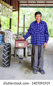 NaKhorn Pathom, Thailand-April 3, 2019: Portrait of Asian adult farm standing for photography in front of his pushcart, the traditional rice farming in South East Asia.