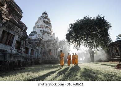 NAKORN RATCHASIMA - SEP 19: Unidentified Thai monks walking with sunlight at Phanomwan Historical Park on September 19, 2015 in Nakhon Ratchasima, Thailand