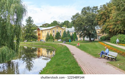 NALECZOW, POLAND. SEPTEMBER 2018: Promenade leading around the pond in Spa Park. In background is historic building of Sanatorium Prince Joseph