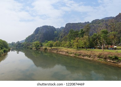Nam Song River and limestone karst mountains near the Tham Chang (or Jang or Jung) Cave in Vang Vieng, Laos, on a sunny day.