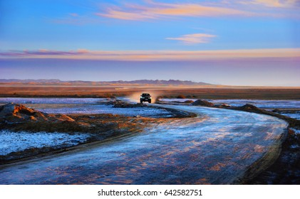 Namak lake, Iran, Middle East. Awesome nature view - twisty road and a car at the background of dried white salt crust, colorful mountain range and dramatic sunset sky in Maranjab desert near Isfahan