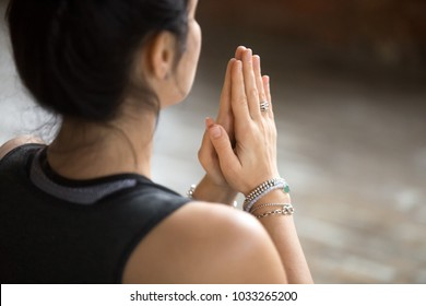 Namaste gesture close up photo, young attractive woman practicing yoga, working out, wearing wrist bracelets and rings, indoor, yoga studio, behind the shoulder view. Contemplation concept