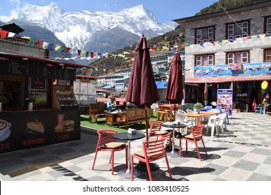 Namche Bazaar, Nepal - March 18, 2018: Town square with restaurant and view of Kongde Ri
