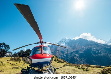 Namche Bazaar, Nepal - OCTOBER 19, 2019: Civil helicopter landed in high altitude Himalayas mountains. Thamserku 6608m mountain on the background. Namche Bazaar, Nepal.