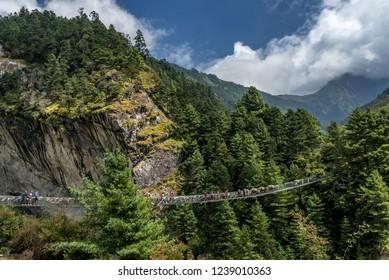 Namche Bazaar, Nepal - October 2, 2018: Trekkers crossing a suspension bridge in Everest Region (Sagarmatha National Park - Himalaya), Nepal.