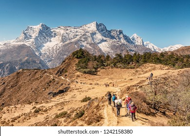 Namche Bazar, Nepal - October 27, 2018: Tourists on the trekking route to Everest Base Camp just outside of Namche Bazar on the way to Everest view Hotel Kongde Ri peak at the background.