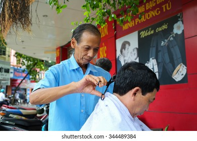 NAMDINH, VIETNAM - Aug 30, 2015: Unidentified barber cut hair on street on Aug 30, 2015 in Namdinh, Vietnam. Barber who doesn't have a shop have to work on street.