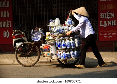 NAMDINH, VIETNAM - DECEMBER 08: unidentified woman sells ceramics on the street on December 8, 2013 in Namdinh, Vietnam. Handmade pottery.