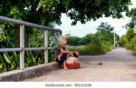 Namdinh, Vietnam - July 13, 2015: an old woman on way back home, resting at the bridgehead