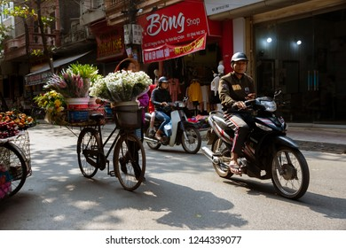 NAMDINH, VIETNAM November 25, 2018: A woman sells flower and fruits in a movable vehicle. small traders, street vendors and exotic food are one of the main attractions for tourists in Vietnam.