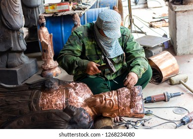 NAMDINH, VIETNAM October 28, 2018: Craftsmen perfect the product made of copper. Namdinh is a well-known province of Vietnam for traditional bronze casting.