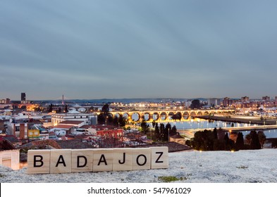 The name Badajoz written in wooden text  with city background