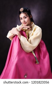 name:Beautiful Korean girl in Hanbok dress. Looks adorable and elegant. standing front of black background. Note to editor: