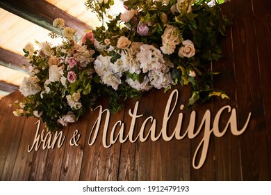 the names of the newlyweds on a wooden board decorated with live roses