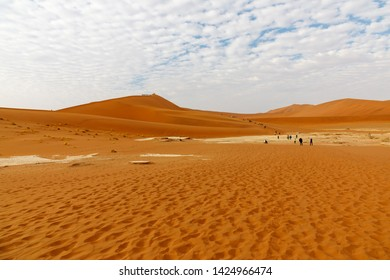 Namib Naukluft National park and Deadvlei, Namibia at dawn with hikers in distance