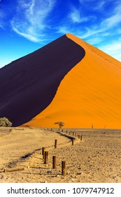 The Namib-Naukluft at sunset. Sharp border of light and shadow over the crest of the dune. The concept of extreme and exotic tourism. Namibia, South Africa