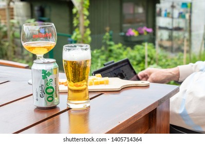 Namur, Belgium, May 22' 2019 image of Carlsberg beer alcohol free in a glass beside a man and his laptop to relaxed after work all day long.