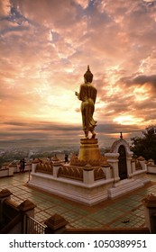 Nan -  December 6,  2014 : A  walking Buddha  against  early morning sky  at Wat Pra That Khao Noi  , Nan Thailand.