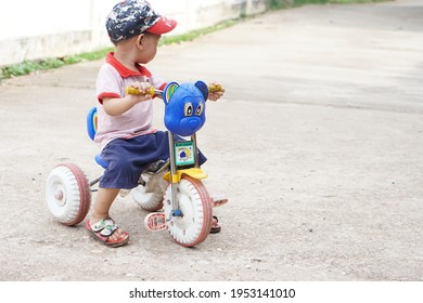 Nan Province, Thailand -April 10th 2021 : Thai cute little boy is riding small tricycle. Concept of skills training and development of muscles, balance and decision making. Childhood activity outdoor.