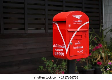 Nan Province , Thailand - April 29, 2020 : The red post box is located beside the street to be a service point for sending  letters.