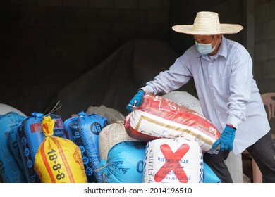 Nan Province, Thailand - July 26th 2021  : Thai rice mill entrepreneur work alone to carry sacks of rice to mill. No labors to hire during Covid-19 crisis. Lock down business