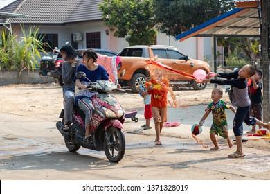 Nan, Thailand, Apr 13, 2019 - Group of kids splashing water to girls driving motorbike on Songkran festival day