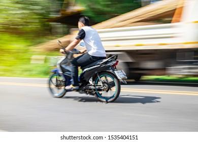 Nan, Thailand, Oct 13, 2019 - Blurry speedy movement of motorbike driving on road
