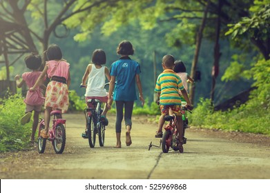 NAN, THAILAND - OCT 24 : Back side of group Asian Undefined happy children riding their bicycle on the street of countryside at BaanPaknai on October 24, 2016 in Nan province, Thailand