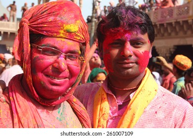 NANDGAON - FEB 28: Unidentified men with face smeared with colors participate in the colorful Holi celebration at Krishna temple on February 28, 2015 in Nandgaon, Uttar Pradesh, India.