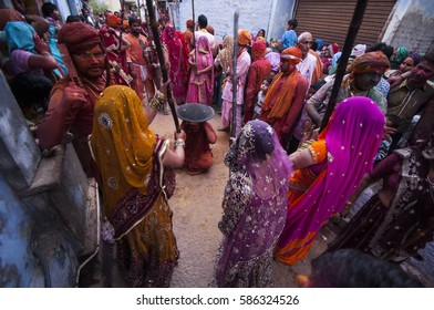 NANDGAON, INDIA, 22 MARCH 2013 : Women beat up men with long sticks as a ritual in the Lathmar Holi celebration, Holi is the most celebrated religious festival in India.